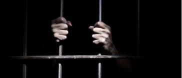 prison barreaux mains prisonnier
